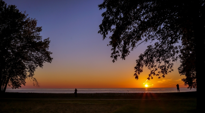 Strangers taking-in the picture perfect sunrise over Lake Ontario