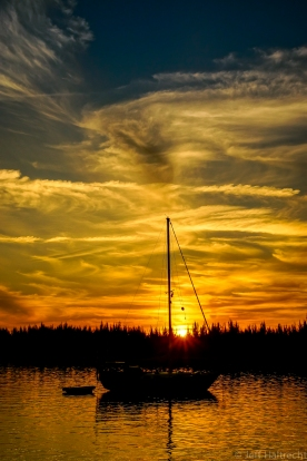 sun setting across sailboat in sea of abaco bahamas