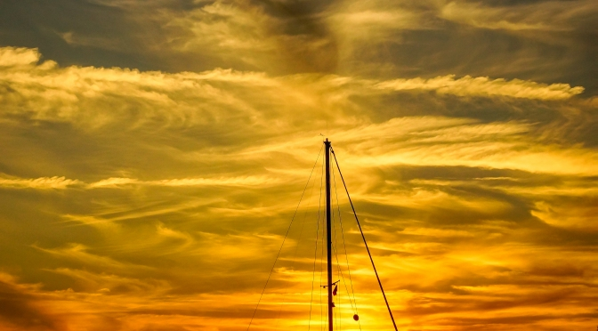 Sun setting across sailboat in Sea of Abaco, Bahamas