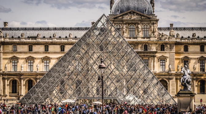 crowds of tourists at the louvre pyramid counting its 673 panes of glass!